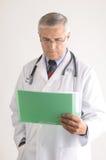 El doctor Looking en la carta de pacientes Foto de archivo