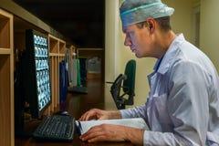 El doctor Looking en el monitor en deber de noche Imagen de archivo