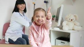 El doctor móvil, muchacha linda muestra la muestra de la aprobación, retrato del niño en la clínica médica, tratamiento paciente