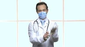 El doctor maduro pone en máscara médica almacen de video