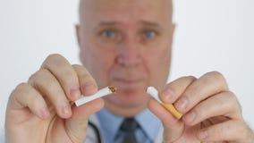El doctor Making a discrepa los gestos que rompen un cigarrillo en campaña anti del tabaco metrajes