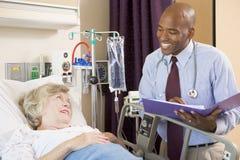 El doctor Making Notes About Patient Imagen de archivo libre de regalías