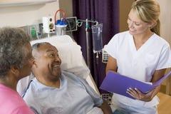 El doctor Making Notes About Patient Foto de archivo