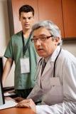 El doctor With Male Technician en la clínica Imágenes de archivo libres de regalías