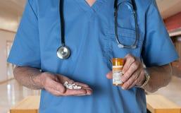 El doctor mayor adentro friega con las tabletas de Oxycodone Imagenes de archivo