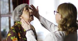 El doctor mayor de la mujer examina a una abuela linda almacen de video