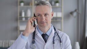 El doctor mayor Discussing con el paciente durante charla del teléfono almacen de video