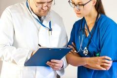 El doctor mayor escribe datos en la tarjeta del paciente, otro doctor mira imágenes de archivo libres de regalías