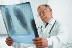 El doctor mayor examina imagen de la radiografía Imagen de archivo libre de regalías