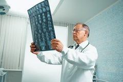 El doctor mayor examina imagen de MRI Imagenes de archivo