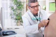 El doctor mayor examina la parte posterior del paciente con el estetoscopio foto de archivo
