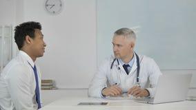 El doctor mayor Listening al paciente en cl?nica almacen de metraje de vídeo