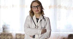 El doctor mayor moderno de la mujer en vidrios y en un vestido médico blanco está mirando a la cámara almacen de metraje de vídeo