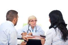 El doctor mayor ofrece consejos médicos a un par imagenes de archivo