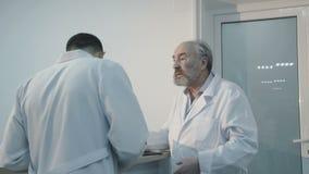 El doctor mayor pide a la enfermera en el mostrador de recepción 4K almacen de metraje de vídeo