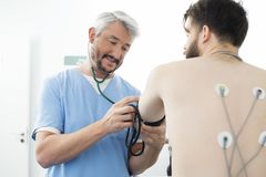 El doctor Measuring Blood Pressure del paciente en hospital imágenes de archivo libres de regalías