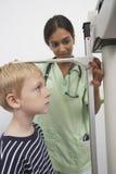 El doctor Measuring Height Of un muchacho imagenes de archivo