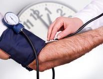 El doctor mide el estetoscopio del examen médico de la presión Imagenes de archivo