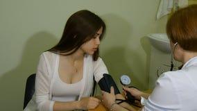 El doctor mide la presión de la muchacha almacen de metraje de vídeo
