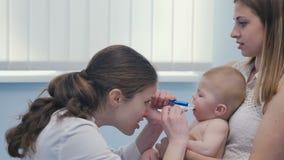 El doctor mira dentro de la boca del pequeño bebé almacen de metraje de vídeo