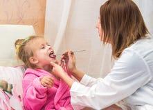 El doctor mira a la muchacha de la garganta del paciente Foto de archivo libre de regalías