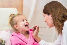 El doctor mira a la muchacha de la garganta del paciente Foto de archivo