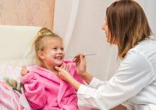 El doctor mira a la muchacha de la garganta del paciente, Foto de archivo libre de regalías