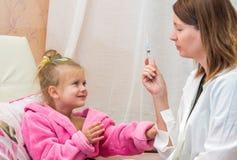 El doctor muestra a la niña de la jeringuilla Fotografía de archivo