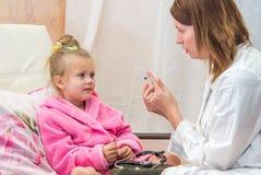 El doctor muestra a la niña de la jeringuilla Imagenes de archivo