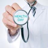 El doctor muestra un estetoscopio con el día de la salud del texto Imagen de archivo