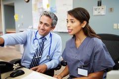 El doctor With Nurse Working en la estación de las enfermeras imagen de archivo