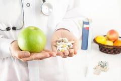 El doctor Nutritionist con la manzana y las píldoras Foto de archivo