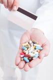 El doctor o el médico del farmacéutico da sostener píldoras y la tarjeta de crédito Fotos de archivo libres de regalías