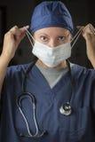 El doctor o enfermera de sexo femenino Putting en mascarilla protectora Fotos de archivo libres de regalías