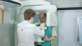 El doctor o el radiólogo que ayuda al hombre mayor que hace el ordenador analiza de dientes almacen de video