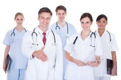 El doctor Offering Hand Shake que se coloca con las enfermeras Imagen de archivo libre de regalías