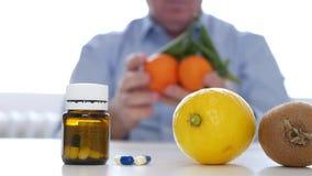 El doctor ofrece el suplemento de las vitaminas de las frutas en vez de píldoras clásicas de la medicina almacen de video
