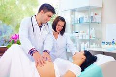 El doctor palpa el abdomen de la mujer embarazada antes de parto Foto de archivo