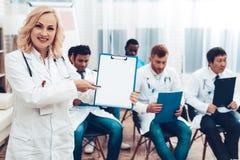 El doctor With Paper Notes de las mujeres Reunión de diagnóstico imagen de archivo