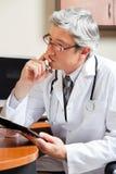 El doctor pensativo At Desk imagenes de archivo