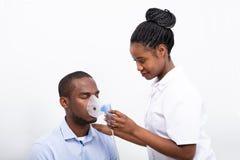 El doctor Placing Inhaler Mask en boca del hombre fotos de archivo libres de regalías