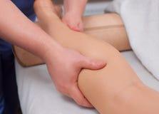 el Doctor-podiatra hace un examen y un masaje de las piernas pacientes del ` s Imagenes de archivo