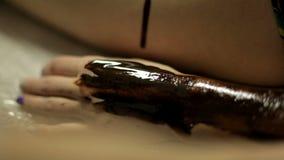 El doctor pone el chocolate caliente en el cuerpo del ` s de la muchacha para el masaje en el balneario almacen de metraje de vídeo