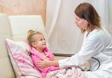 El doctor pone un termómetro de una niña en cama Fotografía de archivo