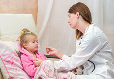 El doctor pone un termómetro de una niña en cama Fotografía de archivo libre de regalías