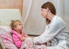 El doctor pone un termómetro de una niña en cama Imagenes de archivo