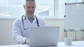 El doctor positivo sonriente At Work Looking en la cámara imágenes de archivo libres de regalías