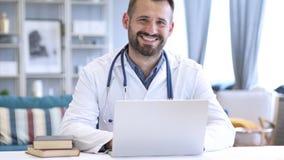 El doctor positivo sonriente At Work Looking en la cámara imagenes de archivo