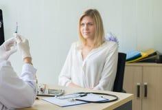 El doctor prepara el donante de la vacuna al paciente asustado de la mujer con la inyección o a la jeringuilla en sitio de hospit imagenes de archivo