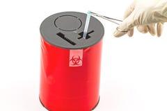 El doctor puso la aguja en cajas de disposición rojas en el fondo blanco Fotos de archivo libres de regalías